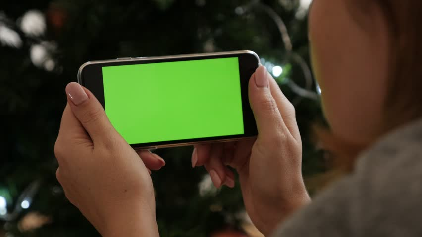 Greenscreen display phone in female hands 4K 2160p 30fps UltraHD footage - Woman looks to green screen gadget in front of Christmas tree 3840X2160 UHD video | Shutterstock HD Video #22082392