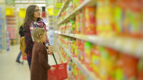 Woman and Girl Choosing Products in Shopping Mall. Mom and Daughter After Puting Some Goods in Red Basket Walk Along Shelves in the Supermarket