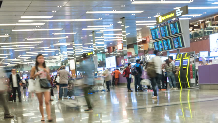 SINGAPORE - FEB 23, 2016 : 4K Timelapse blur background of many passenger walking in front of check-in counter at Changi International Airport, Singapore