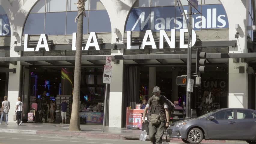 abe4a9f0 LOS ANGELES - OCT 23, 2016: Strange Man Crossing Street La La Land,  Marshall's Store On Hollywood Boulevard Los Angeles California.