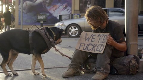 Homeless Man With Beard Throwing Treat To Pet Dog Catching Bone In Mouth In Air On Street Holding Funny We're Fucked Sign In Los Angeles California