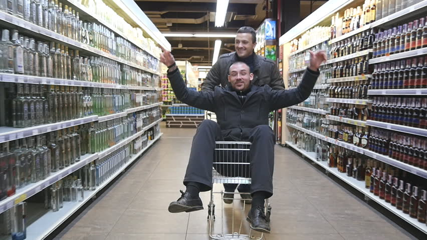 KHARKIV, UKRAINE - NOVEMBER 29, 2016: Young man having fun in the shopping mall driving a shopping cart, his friend riding inside. Happy smiling guy sitting in supermarket trolley at grocery store.