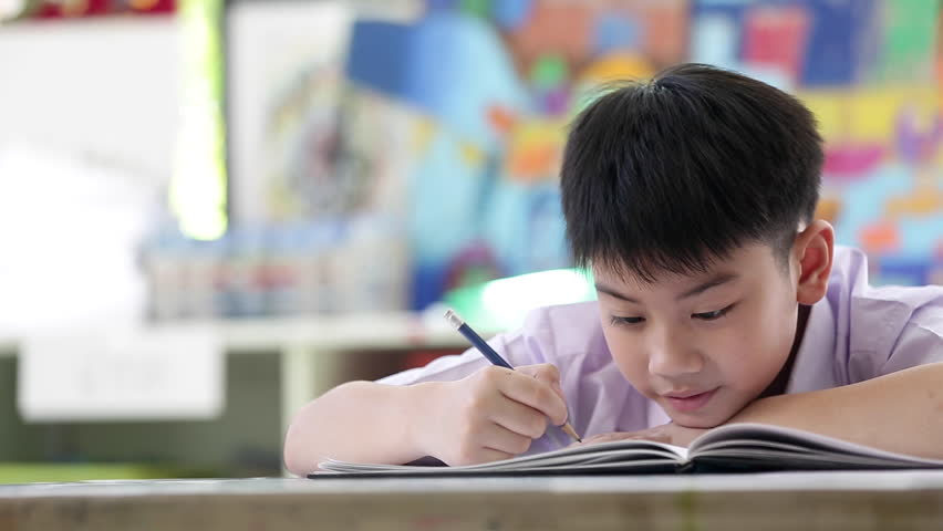 Asian child in student uniform reading and writing to do homework of the school . | Shutterstock HD Video #22135261