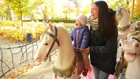 Happy Mother with Long Dark Hair and Little Daughter Riding on Carousel and Laughing Together. Baby Girl Wearing Purple Jacket Sitting on a White Horse in a Roundabout Next to Brunette Woman.