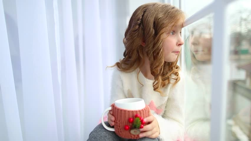 Portrait of cute happy little girl sitting on windowsill, drinking hot tea and looking outside from window. Child holding white mug in winter knitted cover festively decorated with Christmas details.