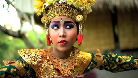 Balinese female artistic dancer performing in ceremonial traditional colorful costume using facial expressions Indonesia South East Asia