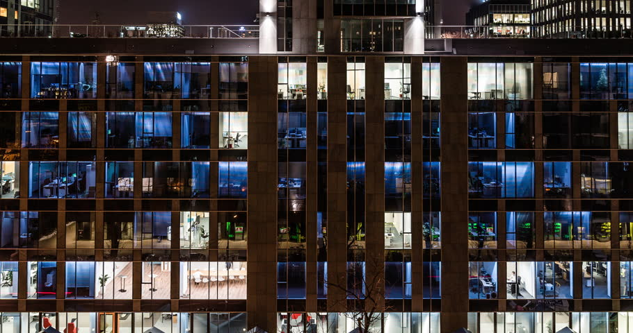 TIME LAPSE: Glass Office Building, Light in the Windows Turning on and off, dusk. 4K. Modern business and conference centre. Career and Employment concept. Corporate life. City rush hour.