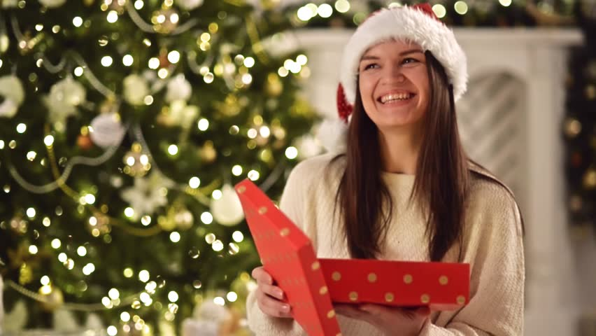 Happy Amazed Woman in Santa Hat, Holding Present in Her Hands, Opens It and Smiles. Pretty Brunette with Long Dark Hair and Santa Clause Cap Openning Christmas Gift Box Next to Xmas Tree | Shutterstock HD Video #22179742