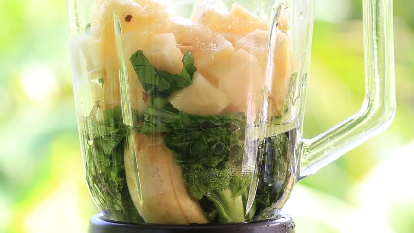 Fruits and vegetables are blended up into a healthy green smoothie. The concept of a healthy lifestyle. Close up
