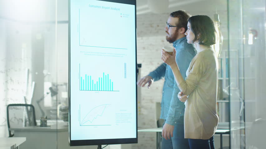 Young Man and Woman Discuss Charts Drawn on Their Electronic Whiteboard. Man Shows Details on the Screen Woman Listens Holding Cup of Coffee in Her Hands.Their Office is developer and Modern Looking. | Shutterstock HD Video #22195384