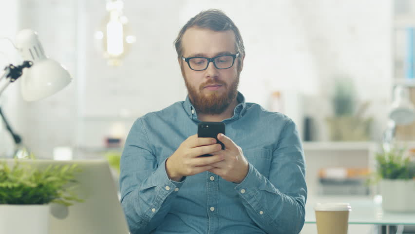 Portrait of a Young Bearded Man with Glasses Sitting at His Desk in a Bright Office Using Smartphone. Shot on RED Cinema Camera in 4K (UHD). | Shutterstock HD Video #22196968