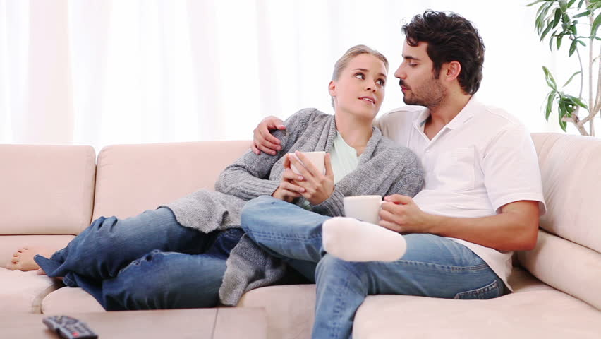 Couple talking to each other while sitting on a couch