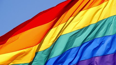 Slow motion gay pride flag blowing in the wind.
