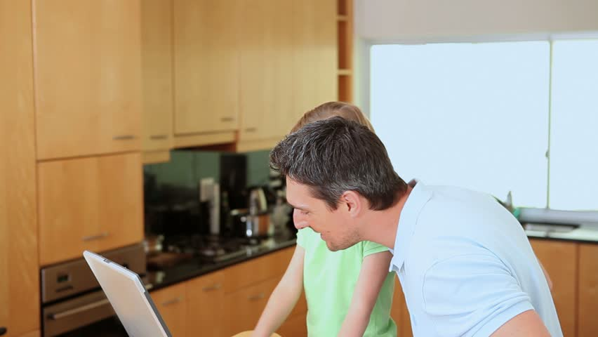 Father and daughter using a laptop in a kitchen