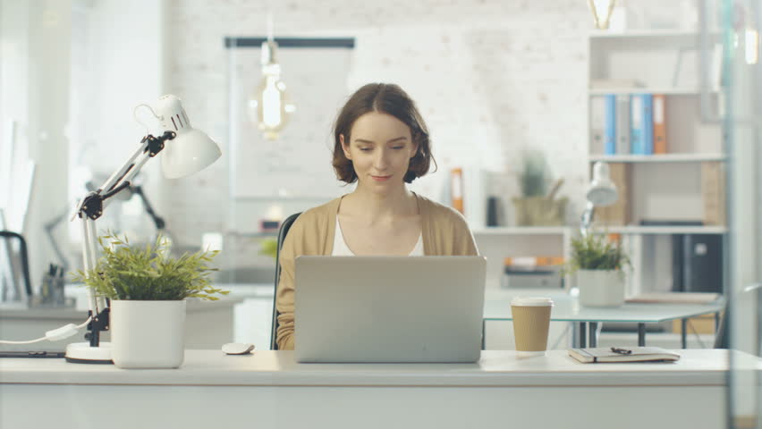 Portrait Shot of a Creative Woman Sitting at Her Desk. Using Notebook. She Sits in a Light and Modern Office. Shot on RED Cinema Camera in 4K (UHD). | Shutterstock HD Video #22232101