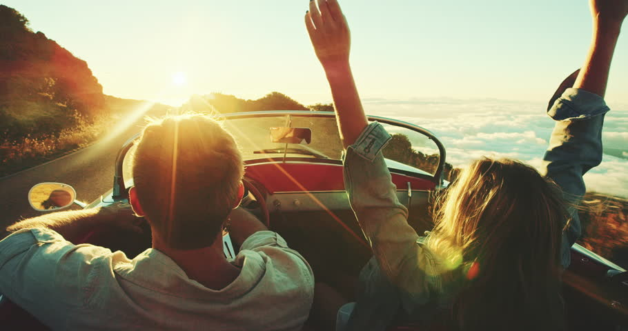 Happy couple driving on country road into the sunset in classic vintage sports car   Shutterstock HD Video #22242838