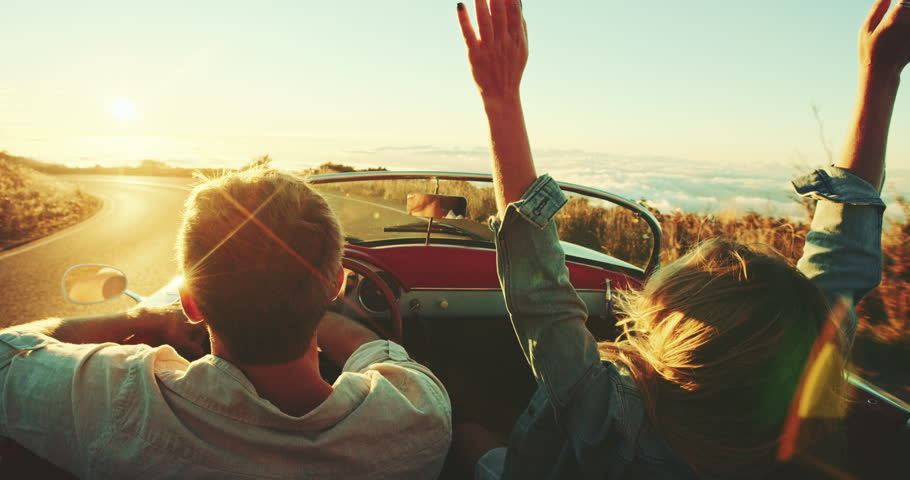 Happy couple driving on country road into the sunset in classic vintage sports car #22242841