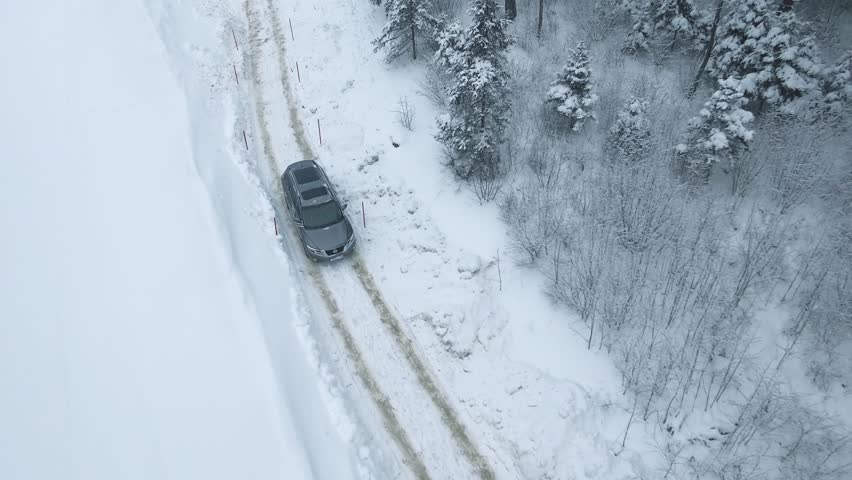 Aerial view of a snowy forest with high pines and road with a car in the winter. Top view of winter road, trees and bushes covered with snow.