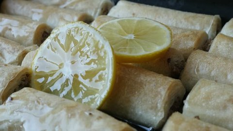 Pouring sweet lemon syrup over filo dough baklava rolls close-up 4K 2160p 30fps UHD footage - Traditional Turkish baklawa phyllo pie with walnuts in sugar 3840X2160 UltraHD video
