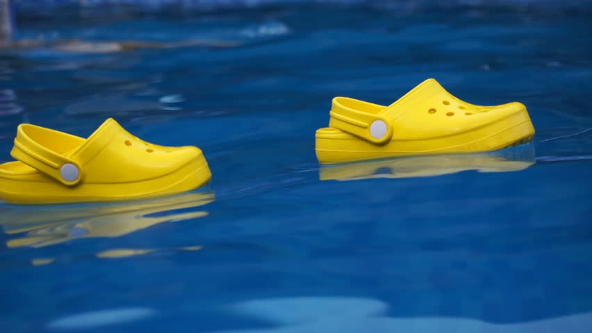 9520427d966 Yellow children s sandals shoes on the water surface in a pool. Mom and  daughter having fun.