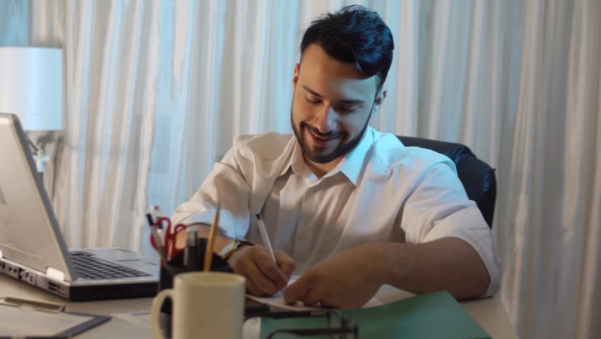 Young trendy businessman in office taking notes and working on the laptop | Shutterstock HD Video #22270021