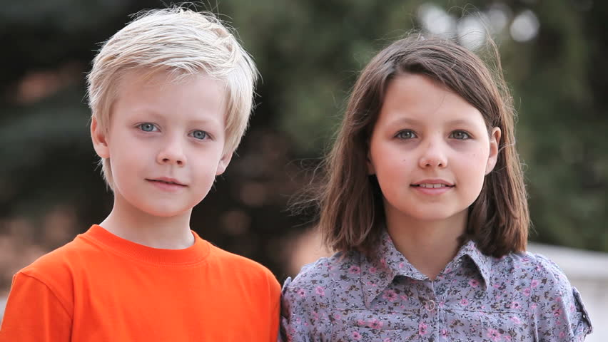 Boy and girl smiling at camera then looking at each other with affection