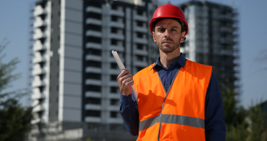 Worker man portrait holding blueprint looking camera under convinced architect expert with plan look camera serious under development site ultra high definition malvernweather Choice Image