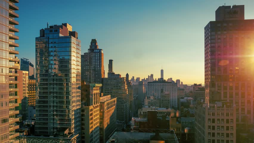 Sunset over Manhattan skyline, sun reflections on buildings.  New York City, NYC. 4K UHD timelapse.