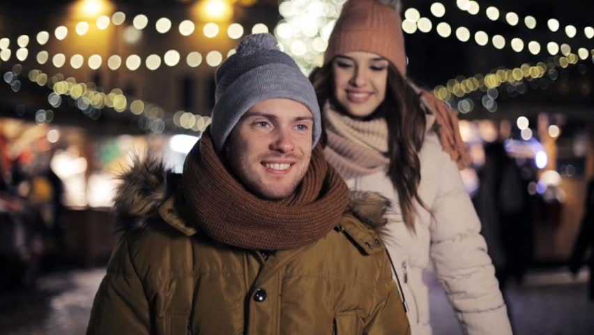 love, winter holidays and people concept - happy young couple dating and hugging at christmas market in evening