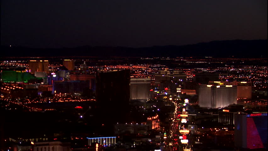 Night High angle from Stratosphere holds 9 seconds roof plate over Las Vegas strip then Pans right over Las Vegas Mountains background (Jan 2004) | Shutterstock HD Video #22300885