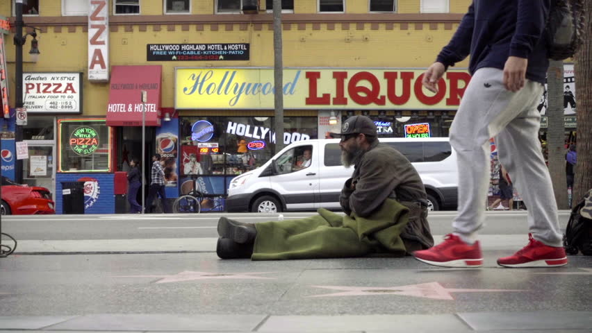 LOS ANGELES - NOV 1, 2016: Itchy Homeless Man Scratching Himself Sitting On Street Hollywood Boulevard Walk Of Fame Stars Outside Liquor Store In 60p In LA CA.