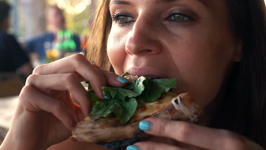 Woman eating pizza in cafe, super slow motion 240fps