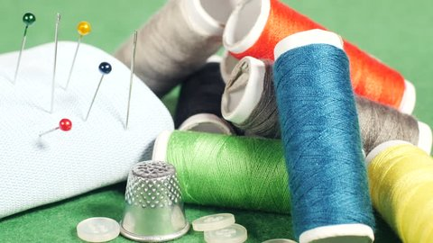 Colorful thread bobbins, buttons, thimble, pincushion with pins and needles, hand adds one more spool and sticks a needle in white cushion, equipment for sewing. Close up, 4K Ultra HD.
