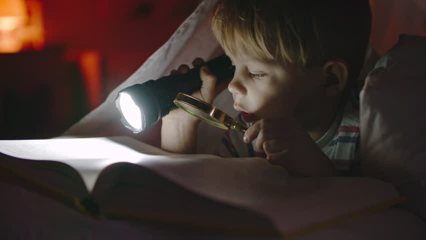 Curious little boy lying in bed in dark holding flashlight and magnifying glass and reading book
