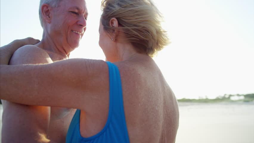Loving seniors mature Caucasian couple swimwear dancing tourism resort healthcare sea coast flare light RED DRAGON | Shutterstock HD Video #22425823