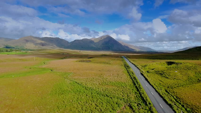The long road in the middle of the Connemara National Park where green grasses are on the field and the cars passing by the road in Ireland
