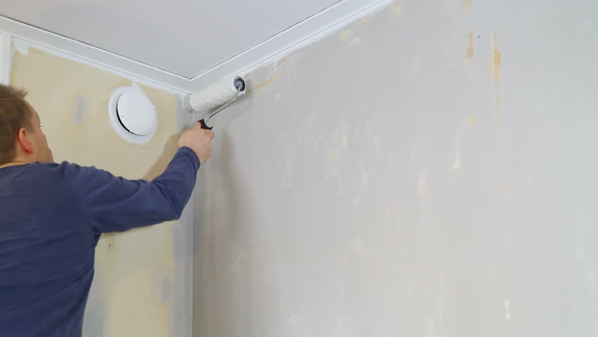 Applaying wallpaper glue using a roller.