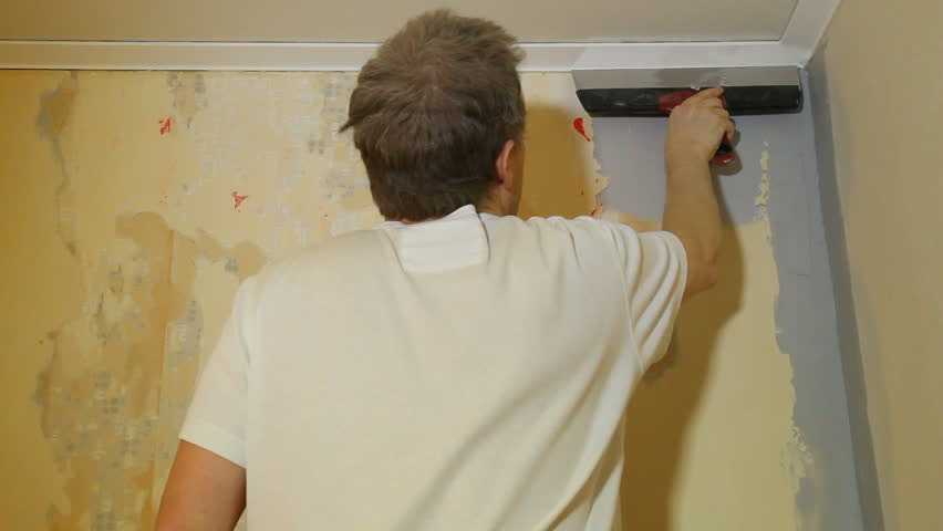 Man spackling a wall with a broad putty knife.