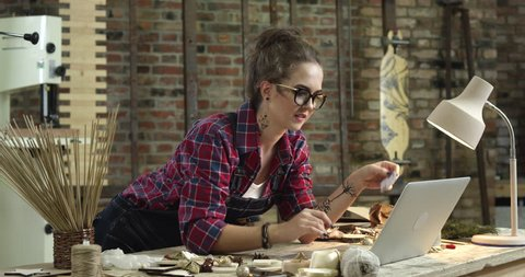 Hipster girl buys online right from her lovely workshop. It's convenient to use credit or debit cards, as you can pay anyone from everywhere/Young Pretty Hipster Buys Online Right from her Workshop