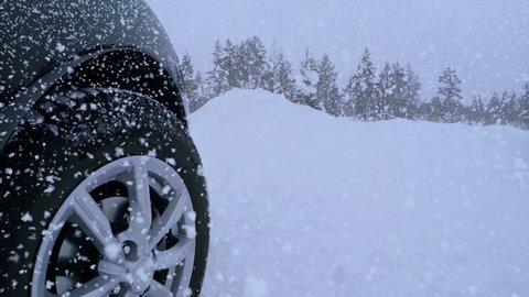 Winter. Road in the forest and lots of snow. Heavy snowfall and front tire of the car