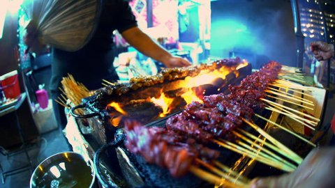Traditional Asian chicken kebab street food cooking outdoor on a coal barbecue fire at night in Singapore South East Asia