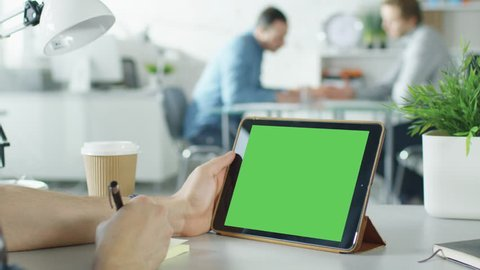 Close-Up of a Man's Hands Holding Green Screen Tablet Computer and Making Notes on Sticky Paper. In the Background Bright Modern Office with People Working in it. Shot on RED EPIC (uhd).