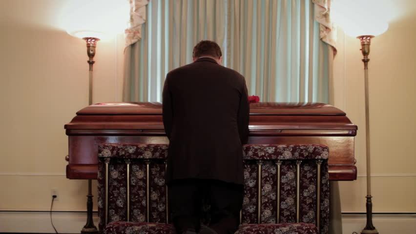 Man kneeling and praying at coffin, funeral service