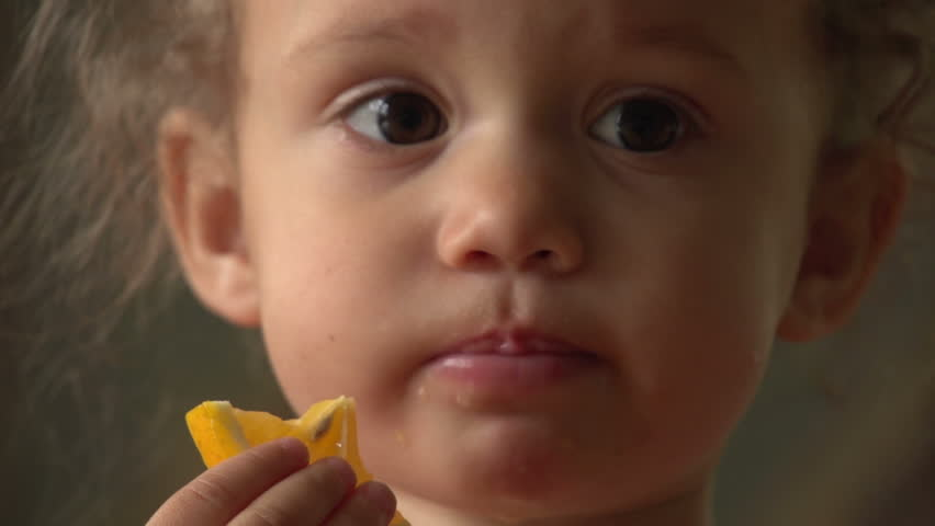 Cute little girl eating an orange, close up #2255002