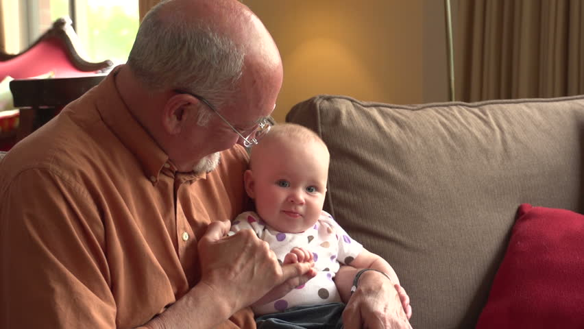 Grandfather on the couch with his baby granddaughter