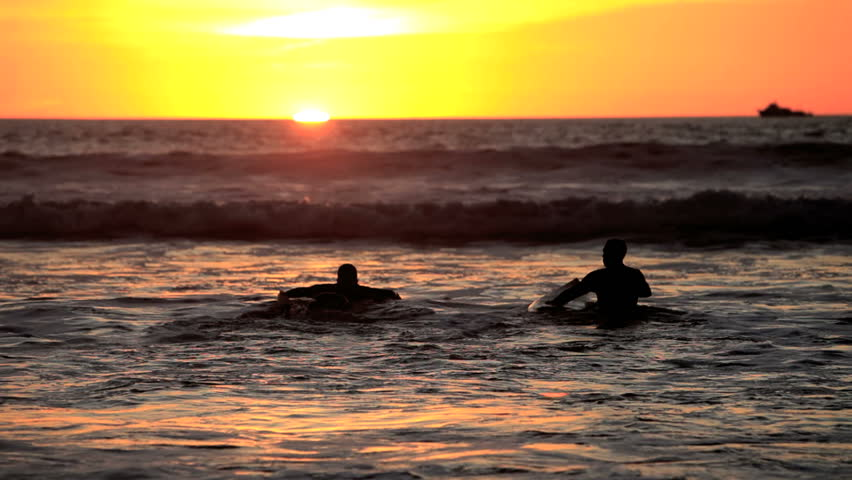 surfers in the water at sunset