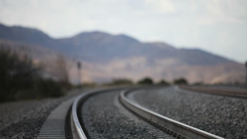 Young runaway walking down the railroad tracks