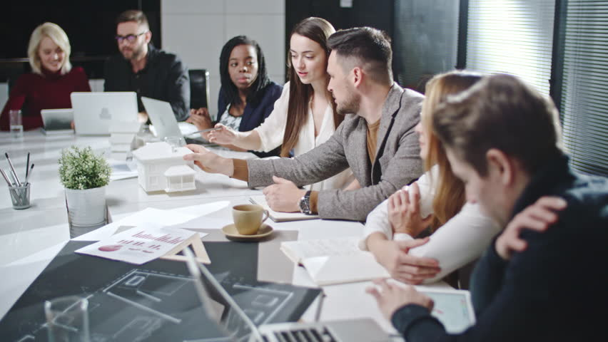 Tilt up of young team working on architectural project together at business meeting | Shutterstock HD Video #22605601