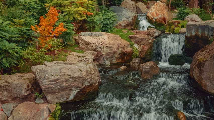 A tilting shot of a quaint Japanese garden with a waterfall during early autumn