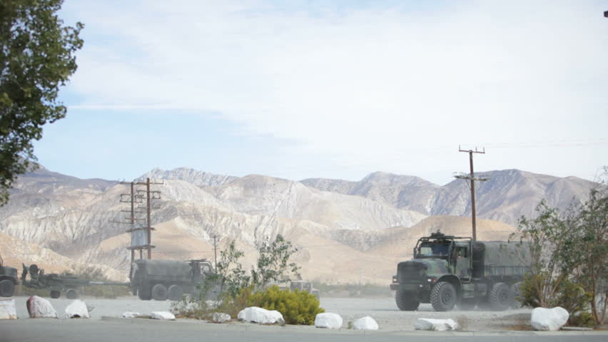 military convoy moving out in desert area